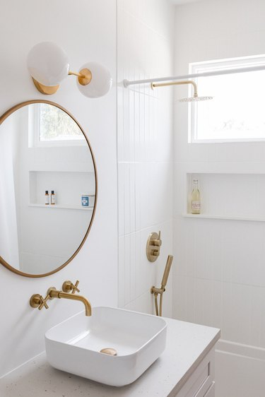 white ceramic vessel sink, gold faucet, round mirror with gold trim, white and round light fixture, white tiled shower with gold fixtures