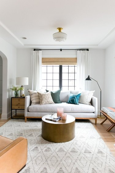 Modern white living room with round coffee table and layered window treatments
