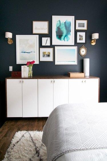 dark blue guest bedroom decorating idea with framed artwork above cabinet
