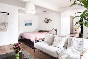 Bedroom with pink linen bedding and white couch