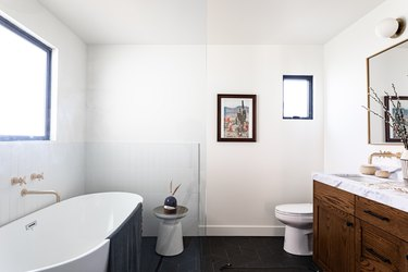 bathroom with bathroom vanity sink, toilet and stand-alone tub