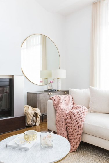 living room mirror idea with chunky knit blanket and large round mirror