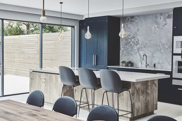 blue and gray kitchen with blue cabinets and blueish gray stone backsplash