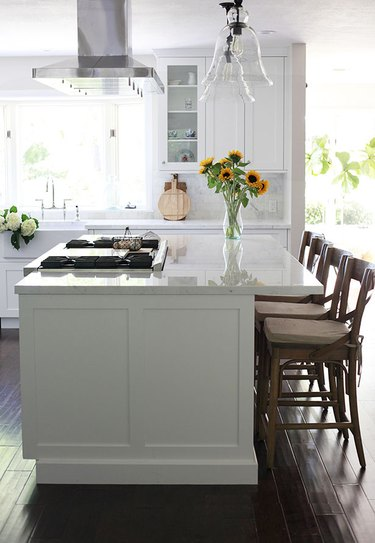 Kitchen island with stove with streamlined paneling
