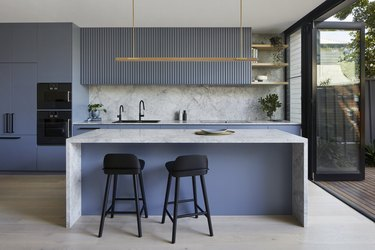 blue and gray kitchen idea with waterfall island countertop and marble backsplash