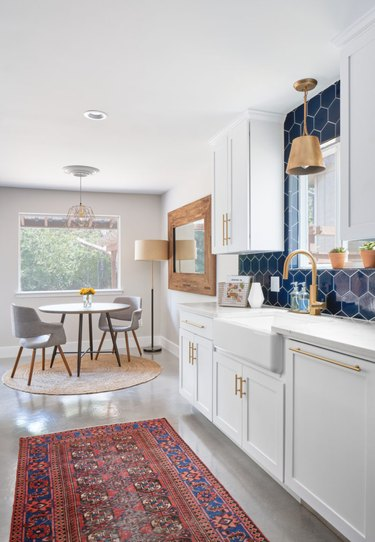 blue and gray kitchen with navy backsplash and gray flooring