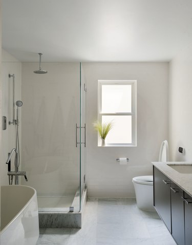 large bathroom, wood floating vanity, white toilet, glass shower with overhead showerhead, tan tile and wall color