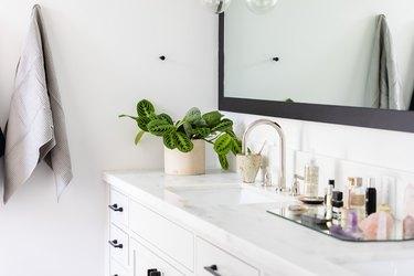 bathroom vaniity with white stone countertop, and large mirror