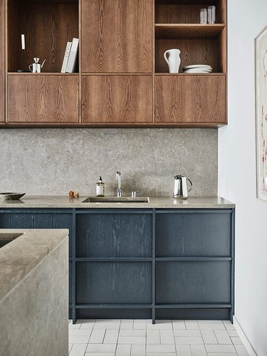 blue and gray kitchen with blue cabinets and gray countertops and backsplash