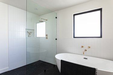bathroom with shower with glass wall, and stand-alone bathtub