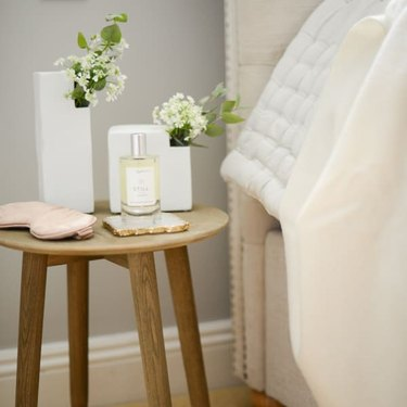 Wooden minimal nightstand with white vases, pillow spray, and blush eye mask
