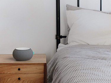 Part of bed and wooden bedside table with gray round sound machine