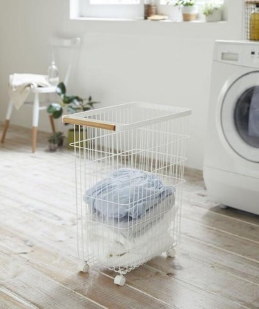 laundry room with basket and white appliance nearby