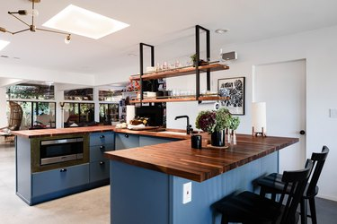 kitchen island decor on u-shaped island with blue cabinets and wood counter