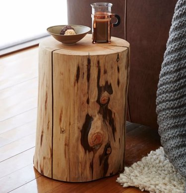 Natural tree trunk end table with tea pot, ceramic bowl, wood floors.