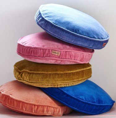 Round velvet throw pillows in light blue, pink, gold, royal blue and orange.