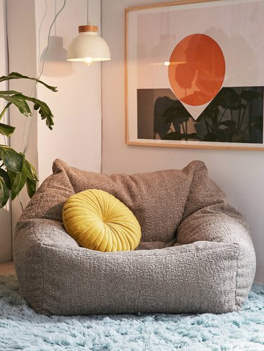 Grey faux sheepskin lounge chair, yellow pillow, light blue shag rub, white pendant lamp, plant, art with orange circle and black band.
