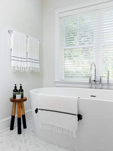 white bathroom trend with freestanding bathtub and Turkish towels