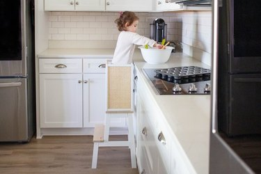 Child standing on learning tower in kitchen