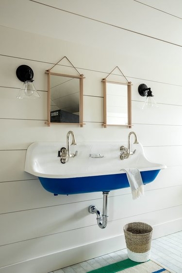 white bathroom trend with blue trough sink and gooseneck faucets