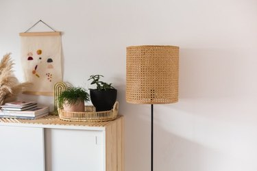 Cane lampshade next to cabinet