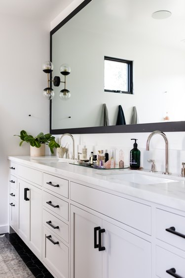bathroom vanity with double sink and large mirror