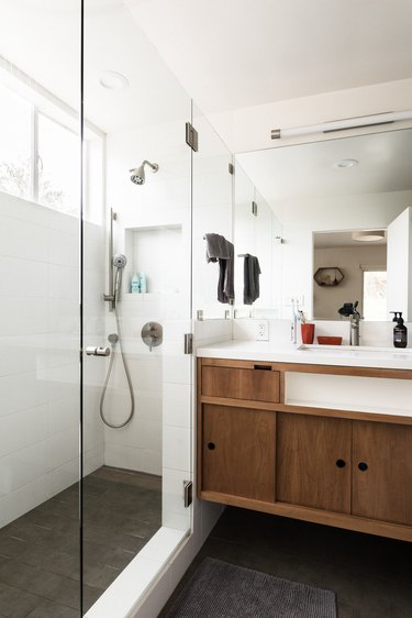 bathroom shower with glass walls, freestanding bathroom vanity with sink and mirror