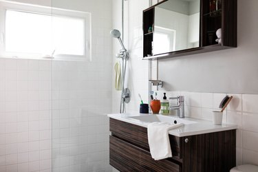bathroom vanity with single sink, white countertop and wood cabinets