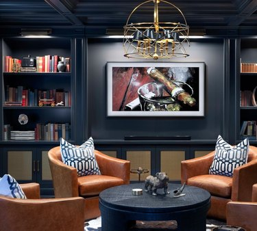 basement lighting in dark gray basement with built in book cases and gold chandelier