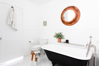 white bathroom with toilet and stand-alone black claw-foot tub