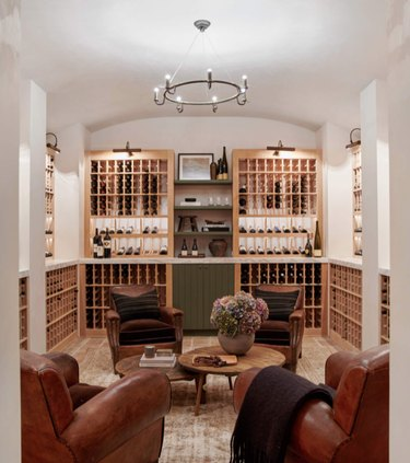 basement lighting in basement wine cellar with natural wood shelves, four leather wing back chairs, wood coffee table, and chandelier