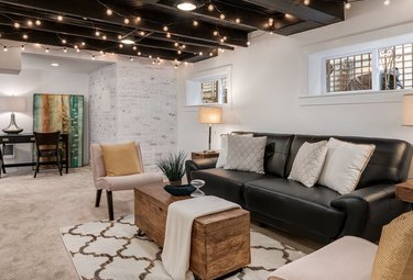 basement lighting in basement with Black leather couch, beige side chairs, wood chest, and criss cross area rug