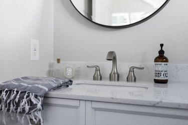 bathroom vanity with light grey cabinets, light stone countertops and circular mirror