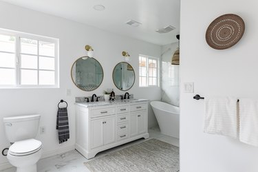 bathroom with double-sink vanity, two circular mirrors, stand-alone tub and toilet