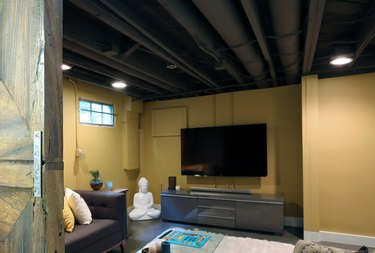 basement lighting in basement with yellow walls, dark gray couch, white area rug, big screen tv, and gray console