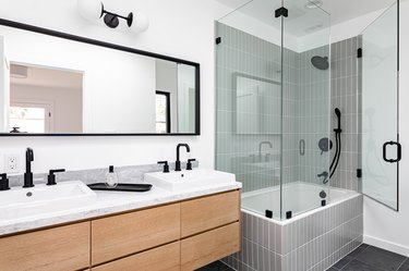 bathroom with tub/shower combo and double-sink vanity