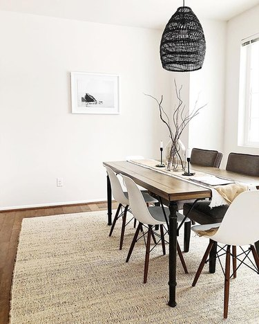 Minimal dining room with wooden rectangular table and white midcentury dining chairs.