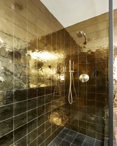 square gold shower tile ideas with gold shower head and glass doors