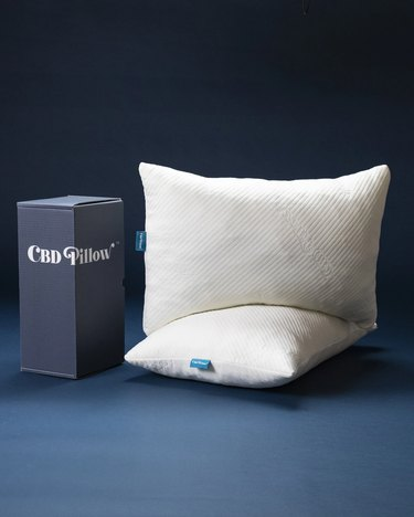 box with text CBD pillow and two pillows nearby