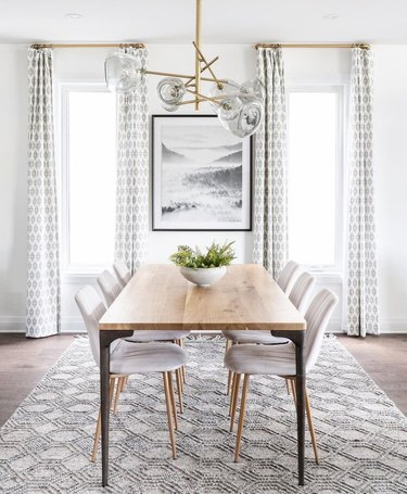 Modern neutral art deco dining room with glass and brass chandelier