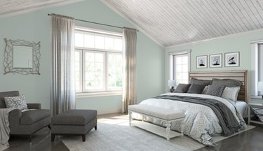 sherwin-williams rainwashed paint color on bedroom walls featuring bed, armchair, ottoman, and curtains