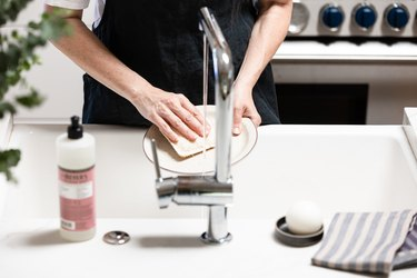 cleaning dish at kitchen sink