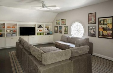 family room wall ideas with vintage posters and gray couch