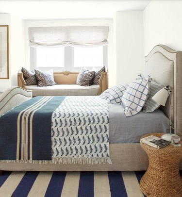Benjamin Moore's Simply White paint color in bedroom featured window seat and bed with blue linens