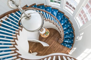 painted white spindles in modern stair railing with blue stair runner