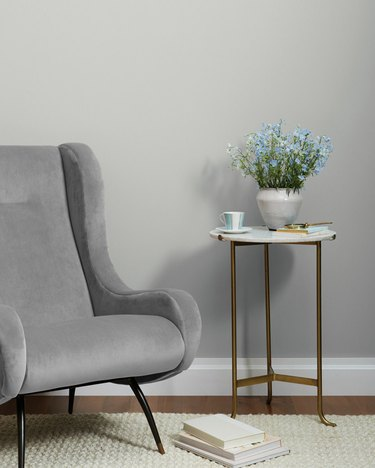 Clare's Seize The Gray paint color on walls in room with grey armchair and side table