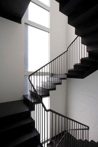 thin black iron modern stair railing with large windows