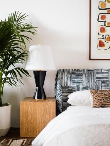 art deco colors in bedroom with black lamp and neutral bedding