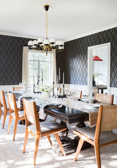Black and brass art deco dining room with wood chairs and patterned wallpaper