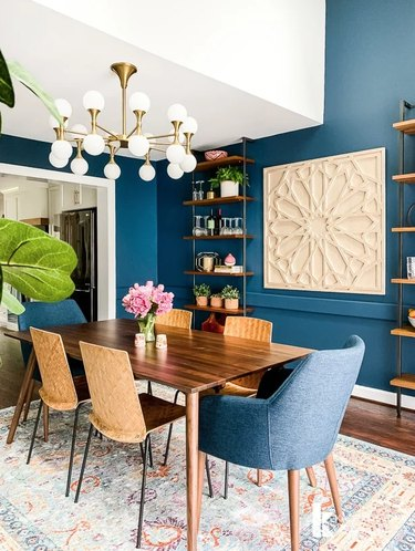 Blue art deco dining room with geometric wall art and modern chandelier